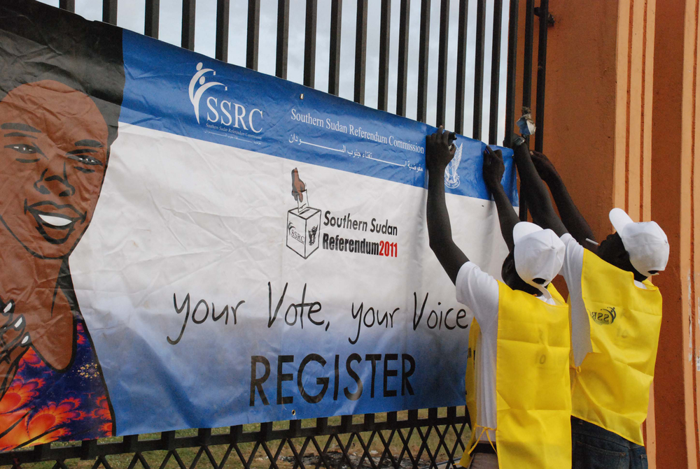 Officials from the South Sudan Referendum Commission hang posters in the southern capital Juba to encourage people to register for a 9 January ballot that is likely to lead to the secession of Southern Sudan