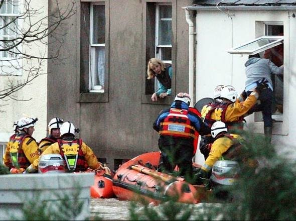 RNLI volunteers rescue survivors from the flooded town of Cockermouth in northwest England in November 2009