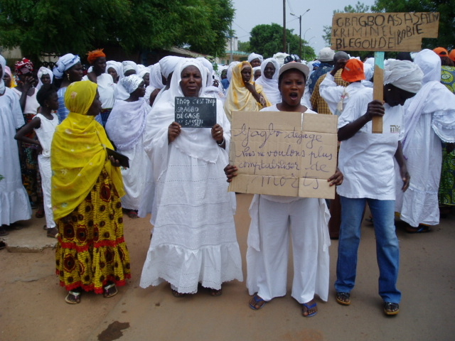 People in the northern Ivoirian city of Odienné demonstrate on 8 March 2011, calling on Laurent Gbagbo to step down. Women held signs that read 'Enough is enough' and 'Gbago, get out. We don't want to keep counting the dead'.