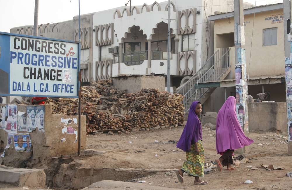 Two girls walk past a campaign billboard in Kano, Nigeria. April 2011