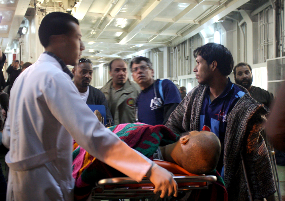 An injured man from Misrata is met by a team of paramedics and doctors from International Medical Corps after arriving in Benghazi on an IOM ship
