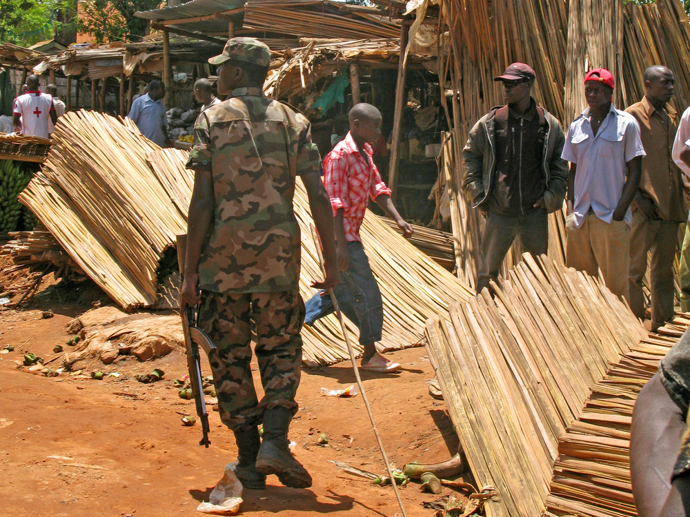 A Ugandan army official patrols the market opposite Kasangati police station in Kampala on 18 April