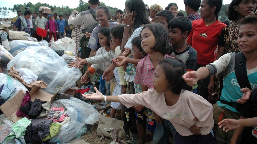 Children receive humanitarian aid brought by the Indonesian Navy in their first landing on the beach in Calang, Aceh on 4 January, 2005