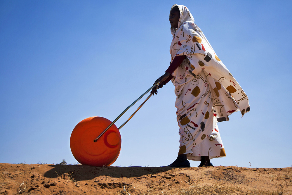 "A woman in El Fasher, North Darfur, uses a Hippo Water Roller, a device for easily and efficiently carrying water. The ""hippo roller"", with its large drum capacity (usually 75 litres), frees women and children from having to spend a large portion of every"