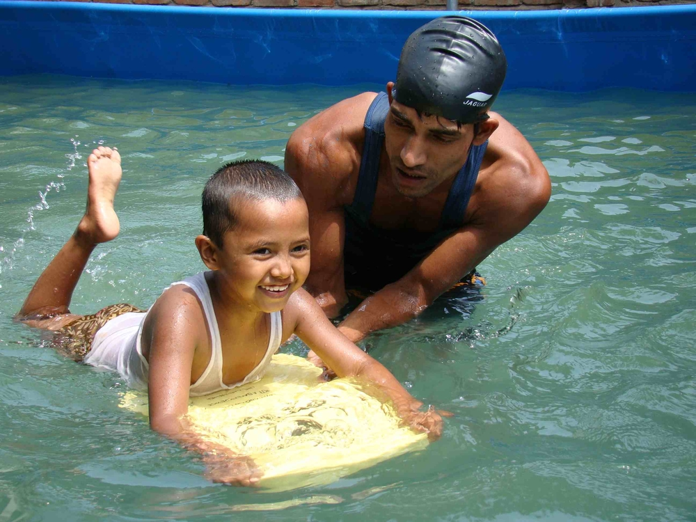 A swimming instructor teaches a child swimming and water-survival skills in Dhaka, Bangladesh