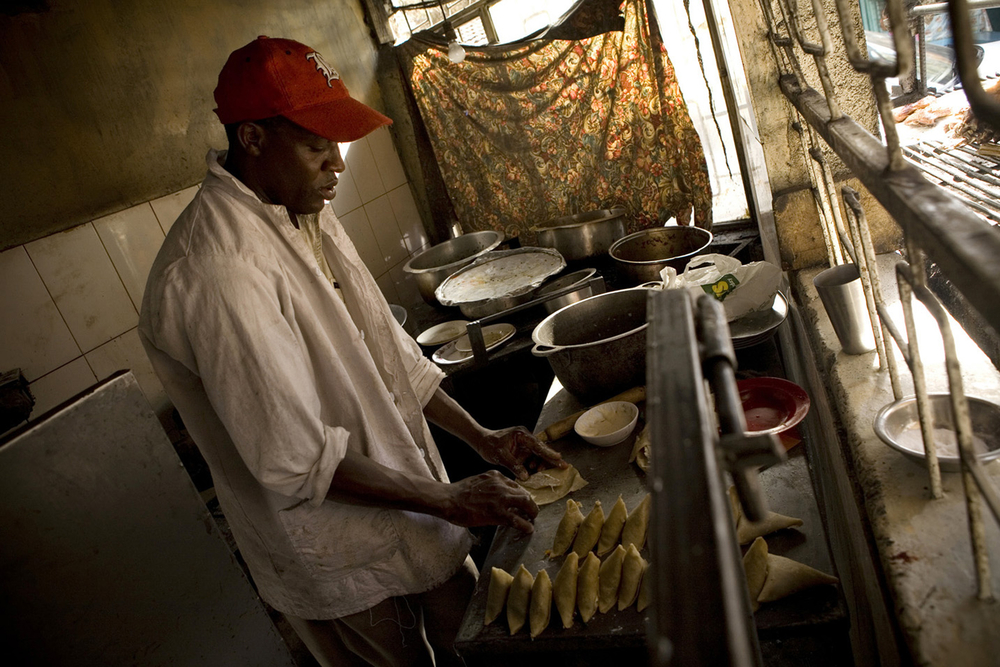 A man prepares food at a local restaurant at the Nairobi City Market in Kenya. According to experts, African nations can break dependence on food imports and produce enough to feed a growing population within a decade