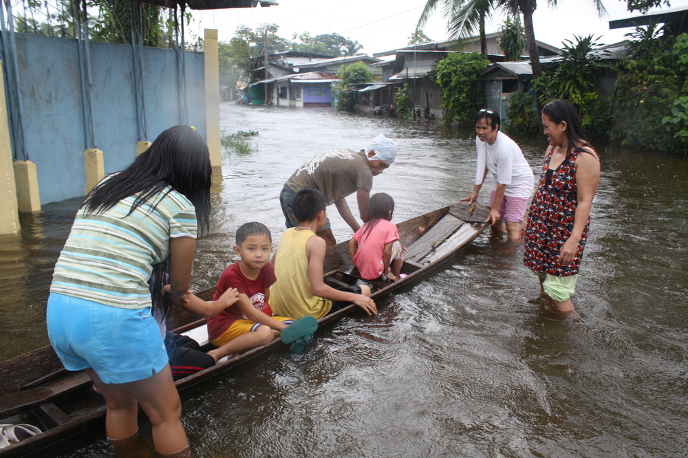 A family works to navigate the flooded streets of Cotabato City, Mindanao [19 June 2011]