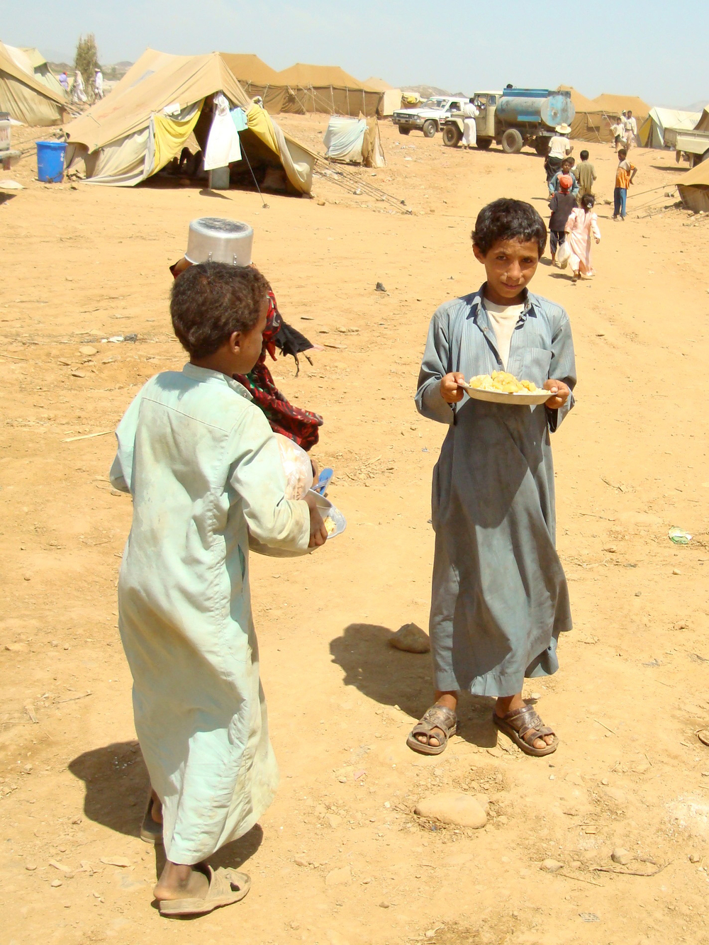 IDP children carrying food for their families in Mazraq One. Recent studies say wide-scale starvation looms over millions of Yemenis due to price hikes