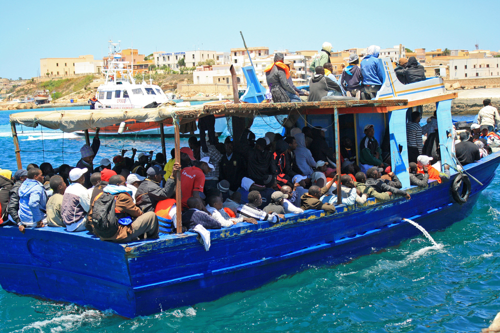 A boat carrying migrant workers and Libyans from Tripoli arrives at the Lampedusa port, escorted by the coastguard