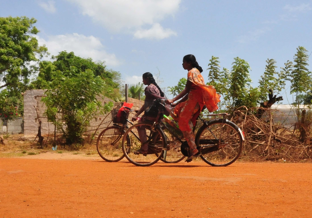 Women riding bicycles along the main road in the village of Allankulam in Mullaittivu District in Sri Lanka