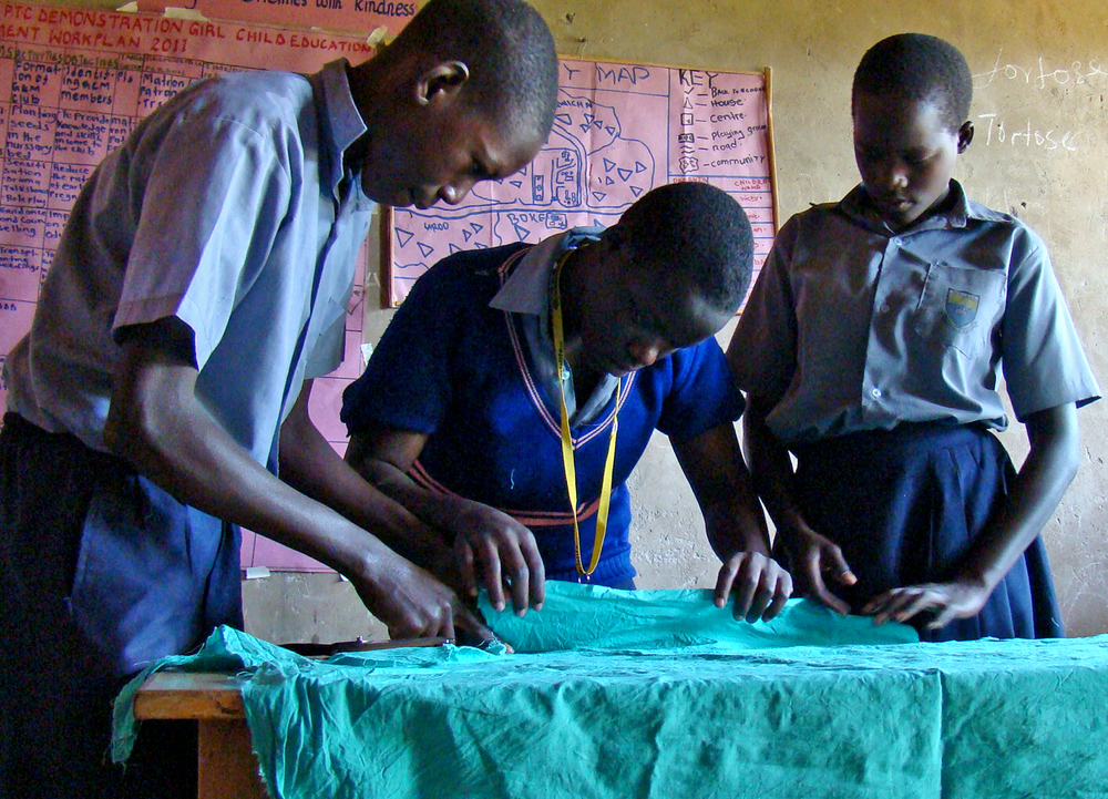 Pupils take measurements of a cotton cloth to be used to make sanitary pads in Uganda