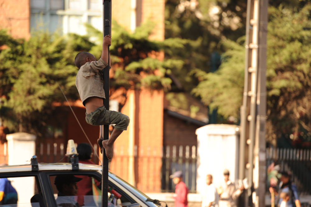 A homeless boy in the Madagascan capital of Antananarivo climbs up a sign post