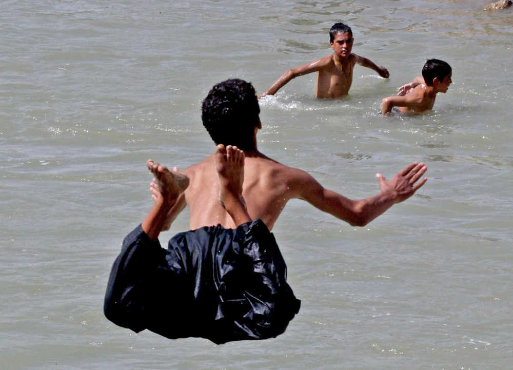 Children and young men swim in an irrigation canal in Arghandab Valley in southern Afghanistan