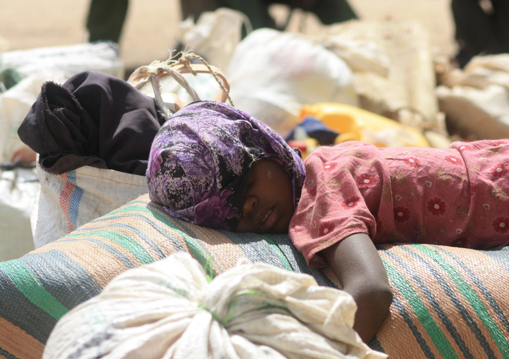 A Somali refugee asleep on a pile of belongings in the Kenyan border town of Liboi, waiting for a ride to Dadaab