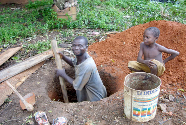 A man digs a latrine for his family in Cote d'Ivoire