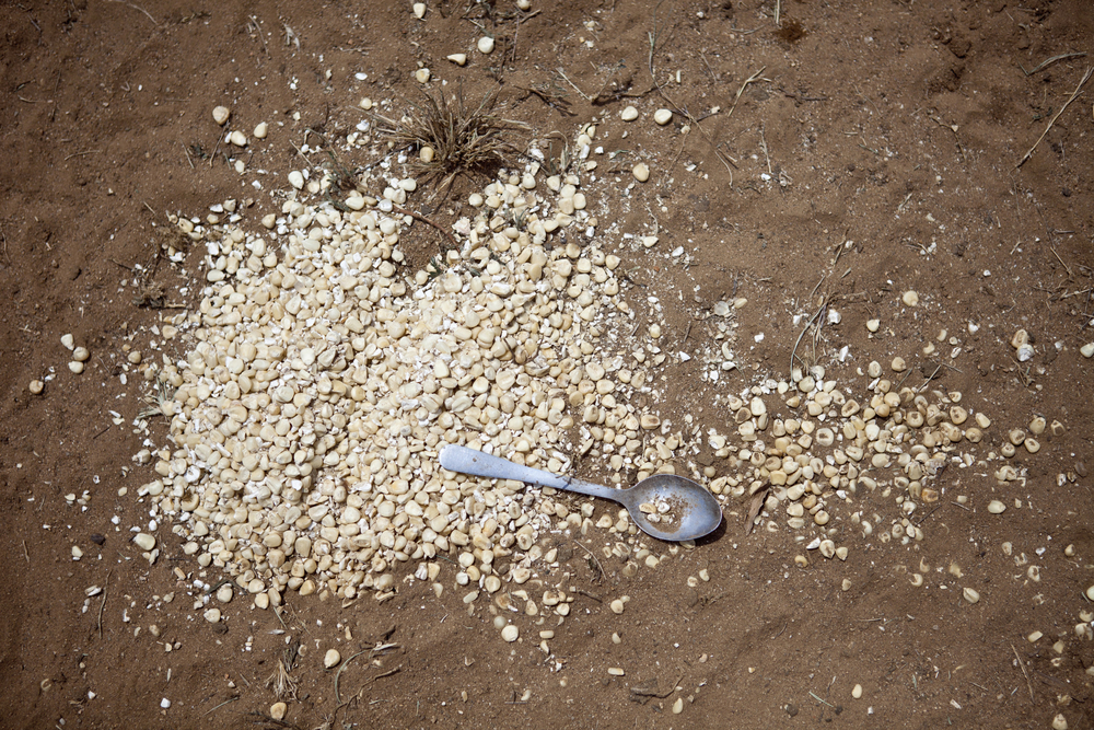 Spilled maize lies in the dirt after Turkana nomads in northern Kenya flee their home fearing attacks from raiders