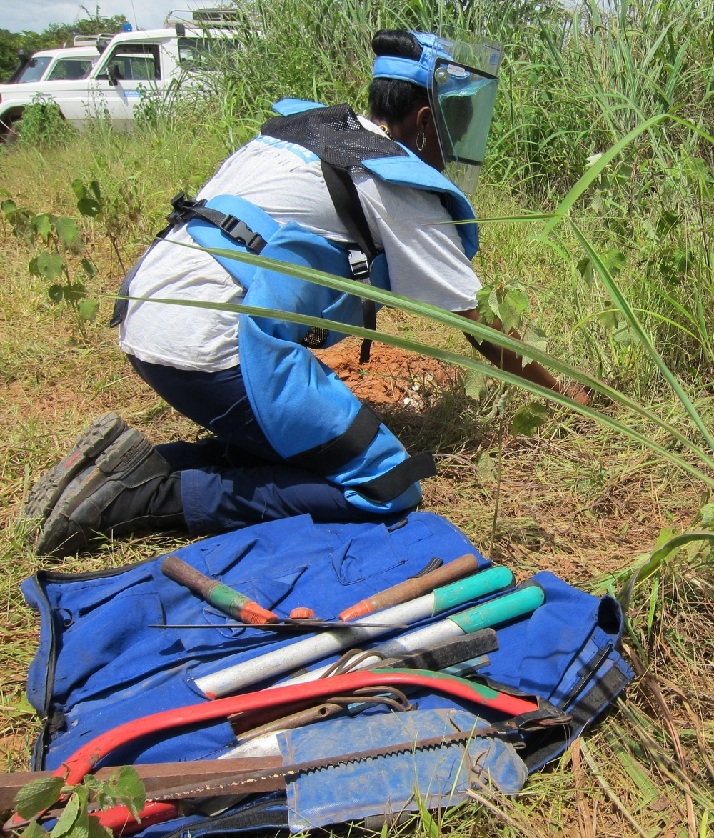 Maibata Sana, a deminer with Handicap International's humanitarian demining program, demonstrates how to remove a landmine manually in Sindone, Casamance, Senegal