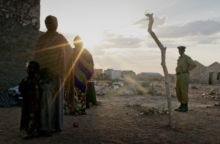 A woman and her young children stand in the evening light at an IDP settlement in South Galkayo, Somalia with armed police standing by