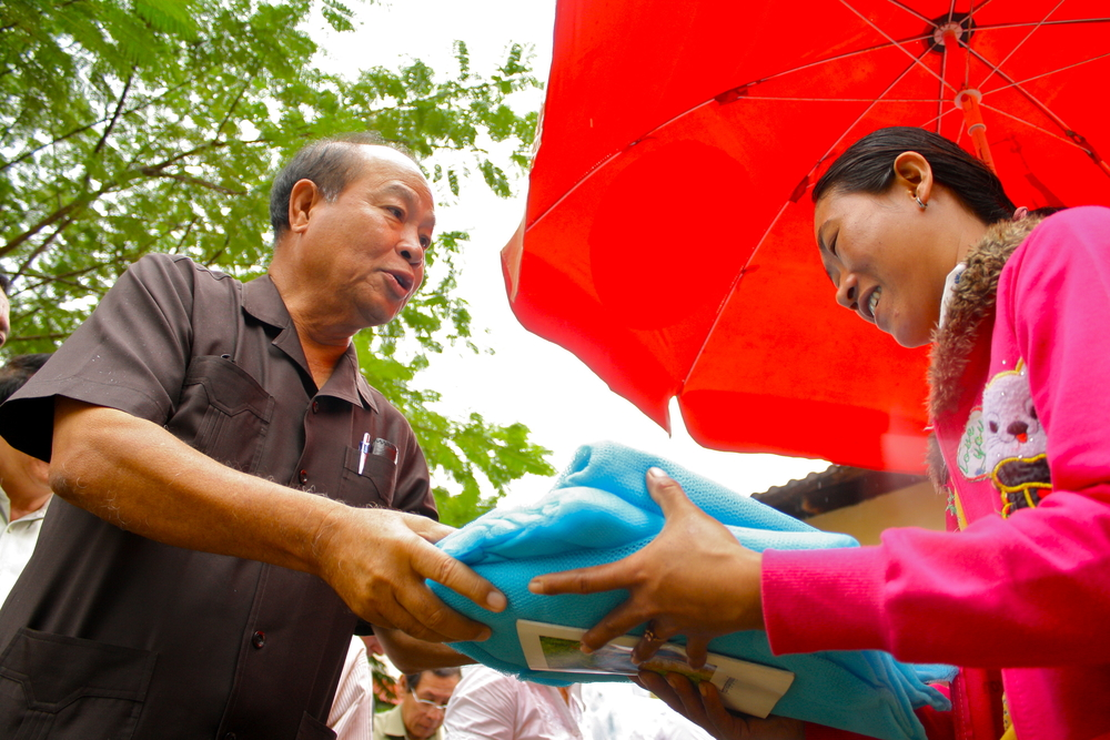 Cambodian Health Minister Mom Bun Heng gives an insecticide treated mosquito net to a resident of a village near a forest in northeastern Cambodia, as part of Asia's largest ever mosquito distribution campaign