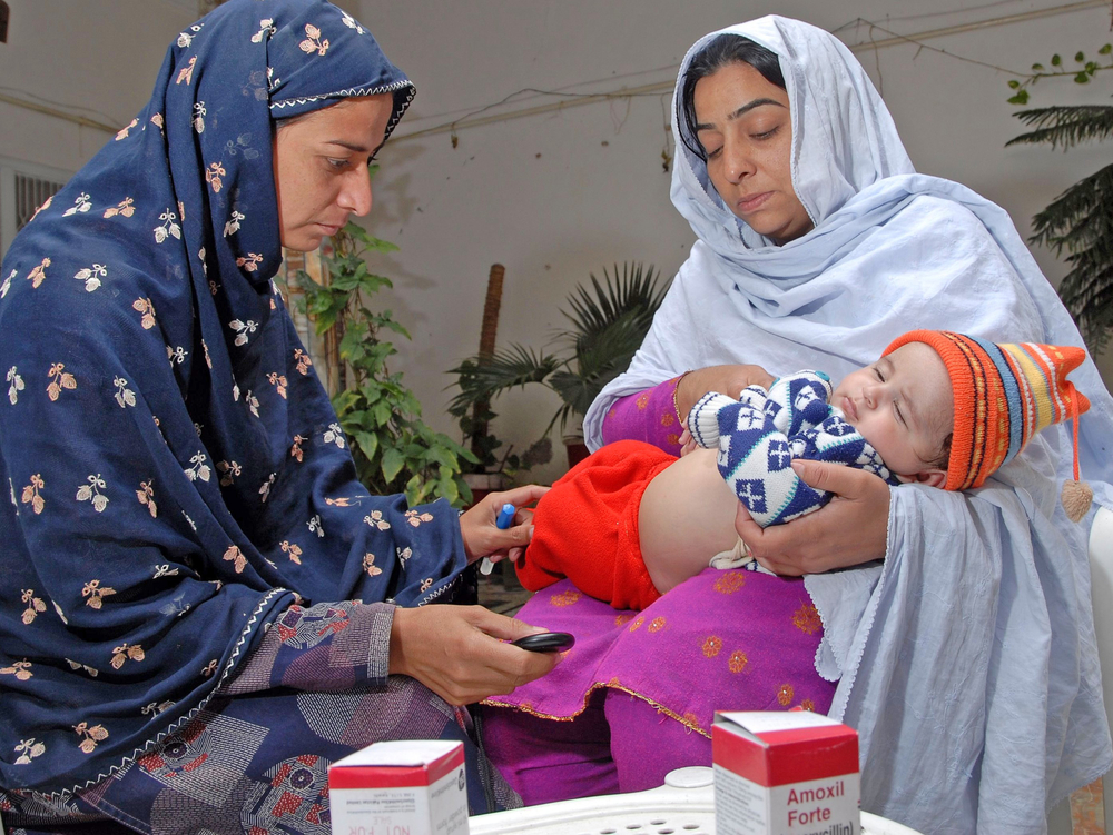 "In Pakistan's Haripur district, a community health worker counts a young child's breaths to diagnose pneumonia. A new Lancet study by Save the Children shows that children treated for severe pneumonia by Pakistan's community-based ""Lady Health Worke"