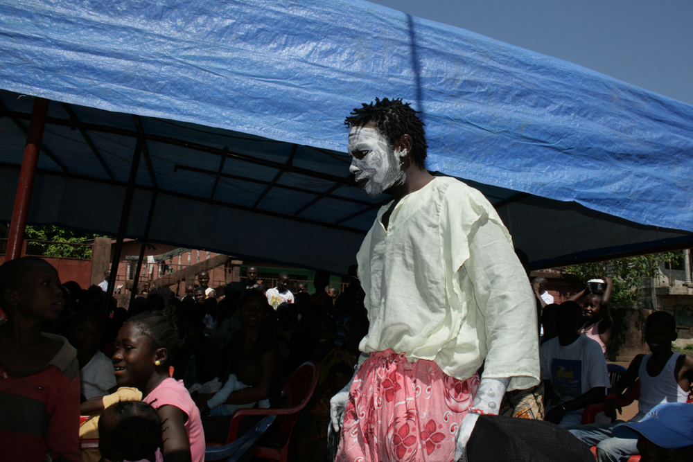 An actor, personifying cholera, tries to creep up on his victims