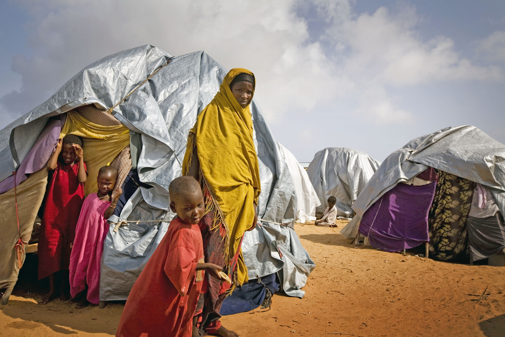 A family stands outside their makeshift tent in BadBado camp in Mogadishu, Somalia