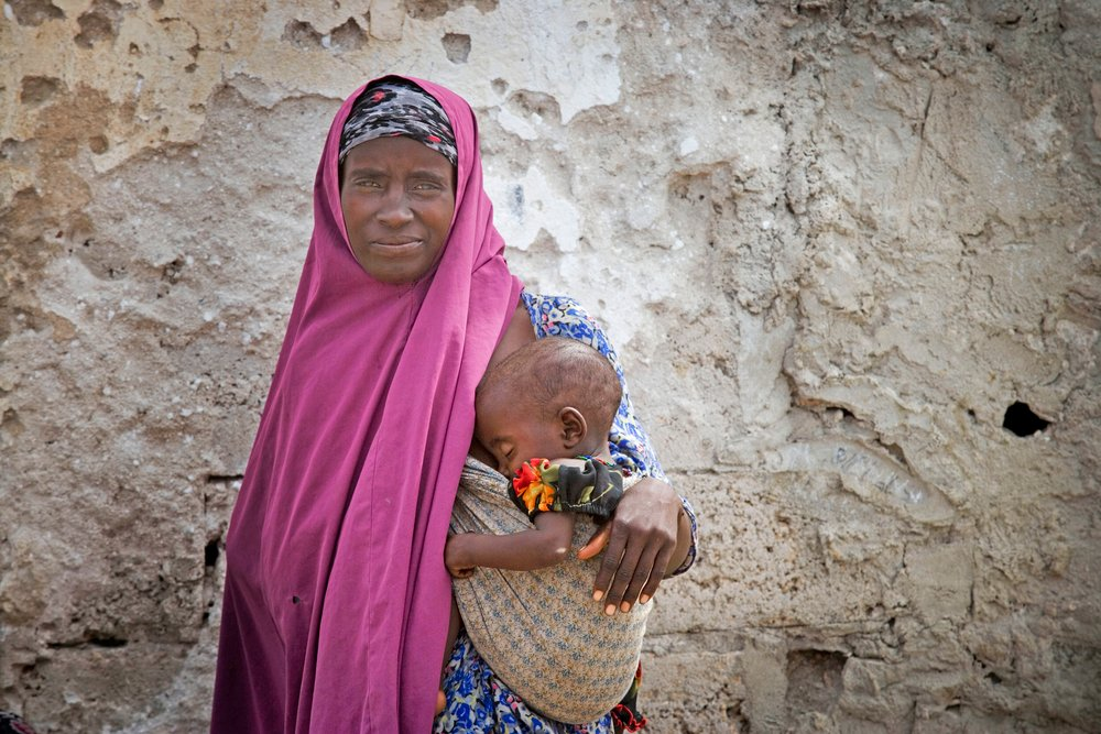A mother and child wait to be seen at the Outpatients Department, AMISOM base in Mogadishu, Somalia