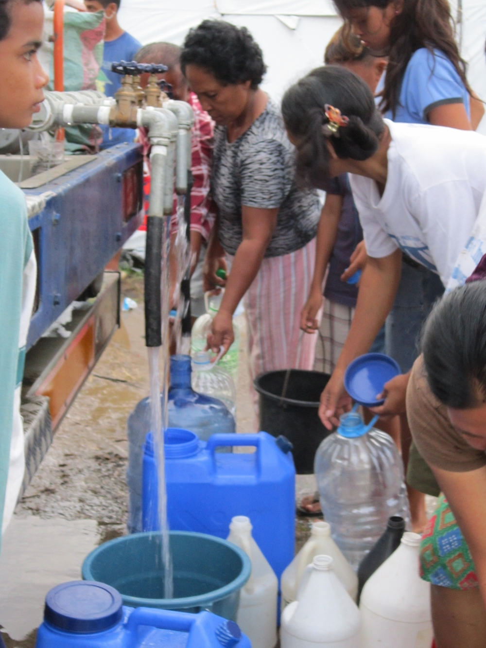 Water distribution at the Calaanan temporary relocation site in Northern Mindanao. Food, water, and shelter remain urgent needs one month after typhoon Washi struck