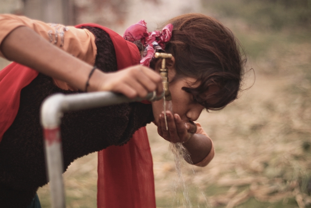 A girl drinks directly from a public tap in Nawalparasi installed