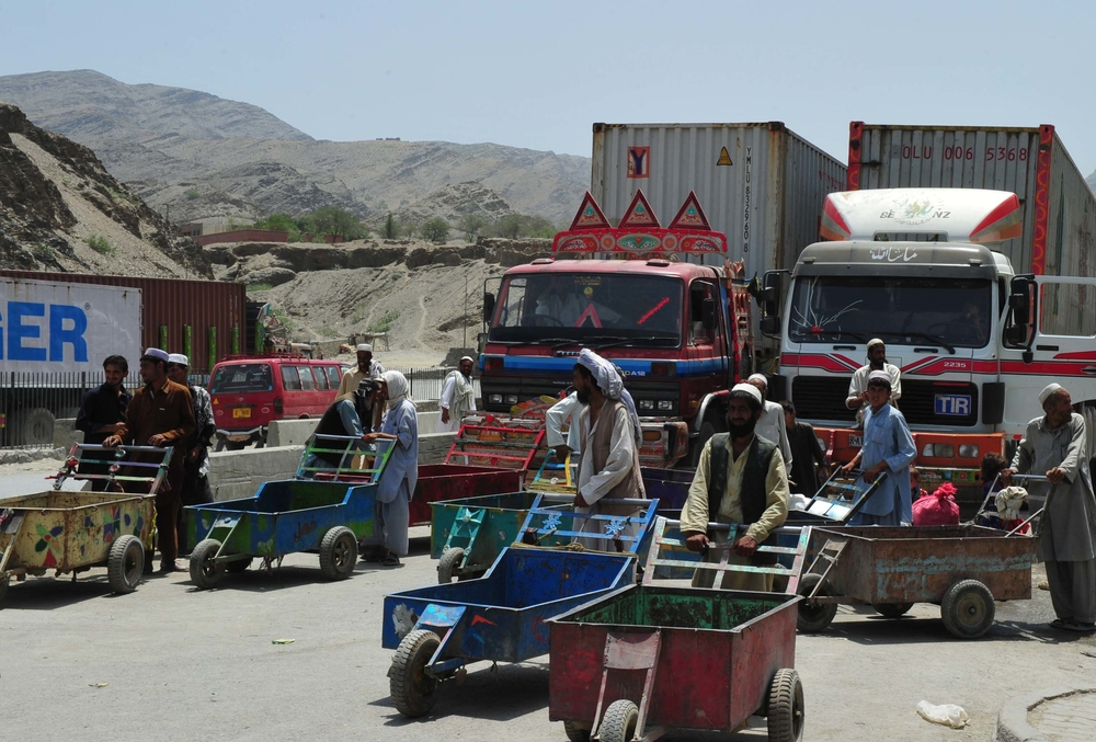 Afghan refugees, living just across the border in Pakistan, search for work at the border by offering to take luggage across.