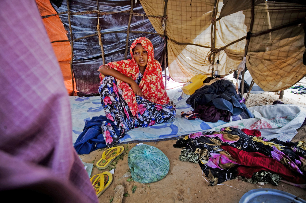 An IDP sits in her temporary shelter in the Wardhiglay area of Mogadishu, Somalia