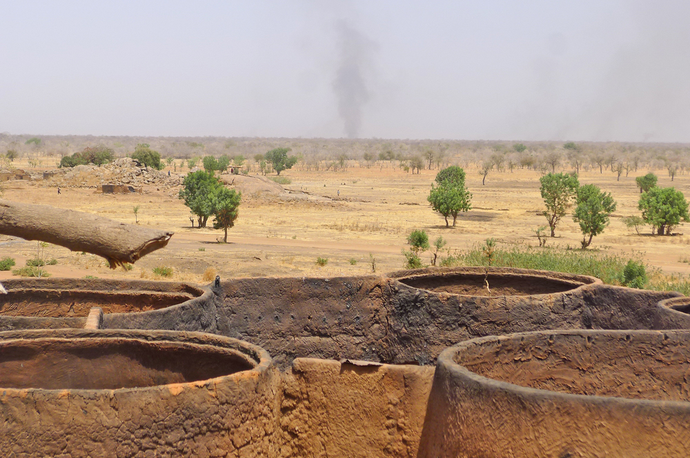 Burnt houses in Dar, with smoke rising from air raid on the horizon, South Kordofan