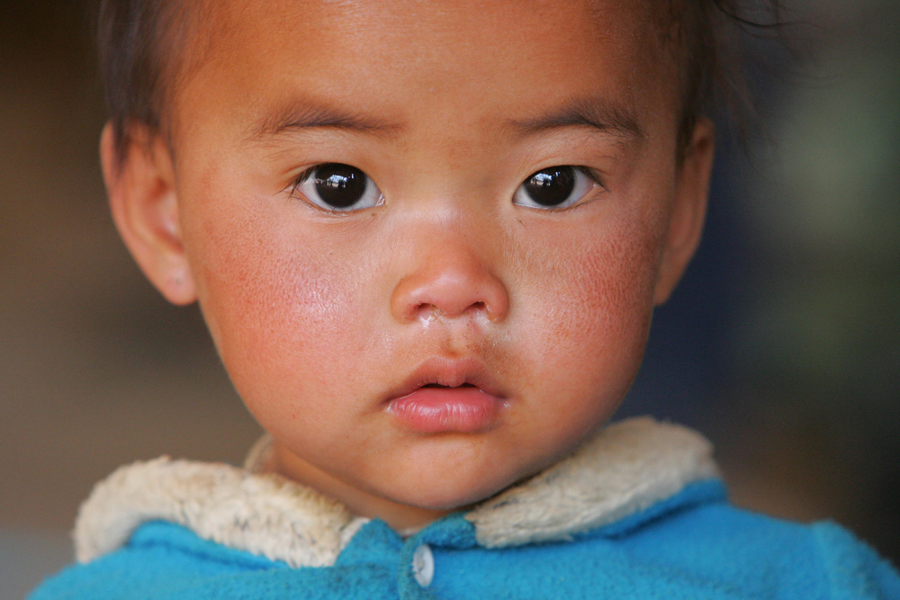 A young Karen child along the Thai-Burmese border looks to the camera. Reaching those in need has not always been easy
