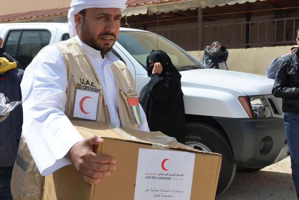 A member of the UAE (United Arab Emirates) Red Crescent distributes aid to Syrian refugees in the northern Jordanian border town of Mafraq. UAE has been active in providing aid in Jordan, but has not done the same inside Syria