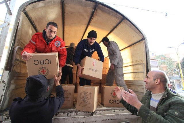 Local people help Syrian Arab Red Crescent volunteers unload food parcels from trucks in the main square of Bludan, Syria, at an impoverished warehouse donated by a local businessman