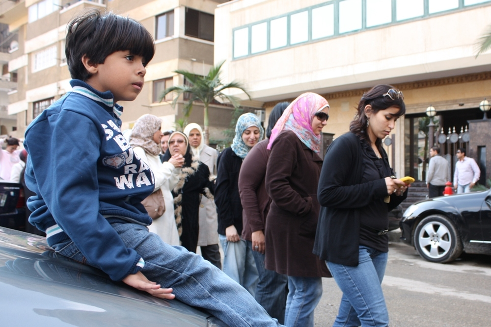 A young Egyptian boy waits while his mother stands in line to vote during the first free and fair parliamentary elections in Egypt in November 2011