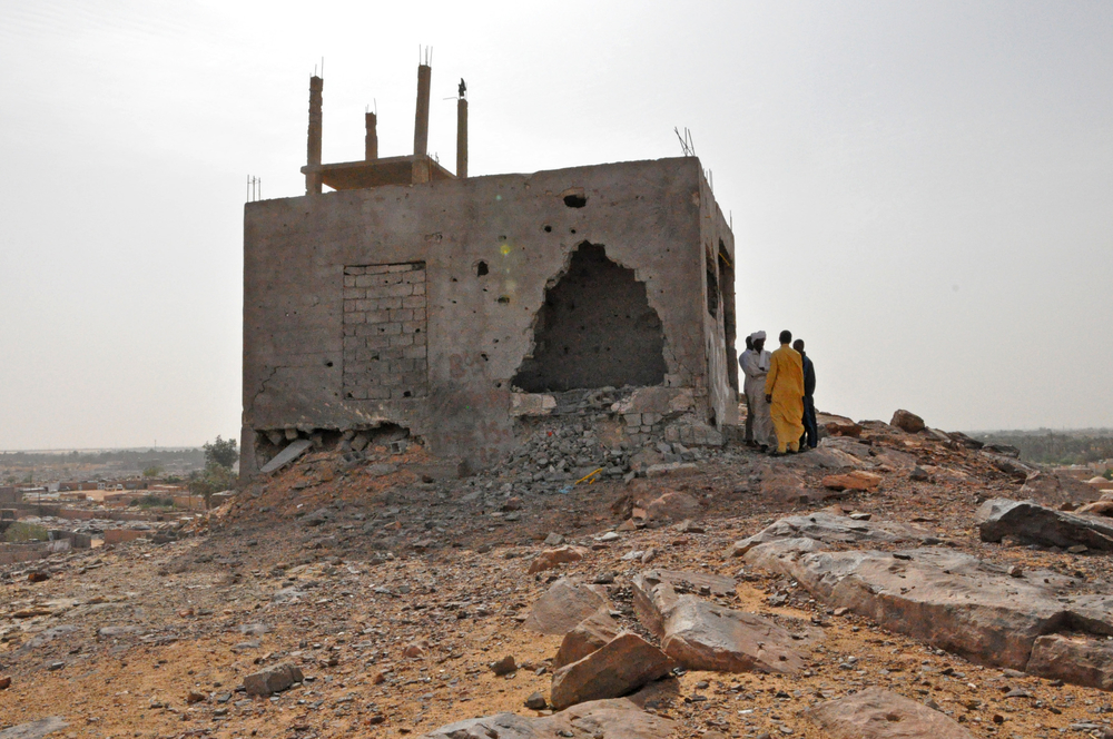 A group of Tubu from Tayuri stand outside the remains of an building which they said was used as a both a refuge and vantage point for shooting during the attacks
