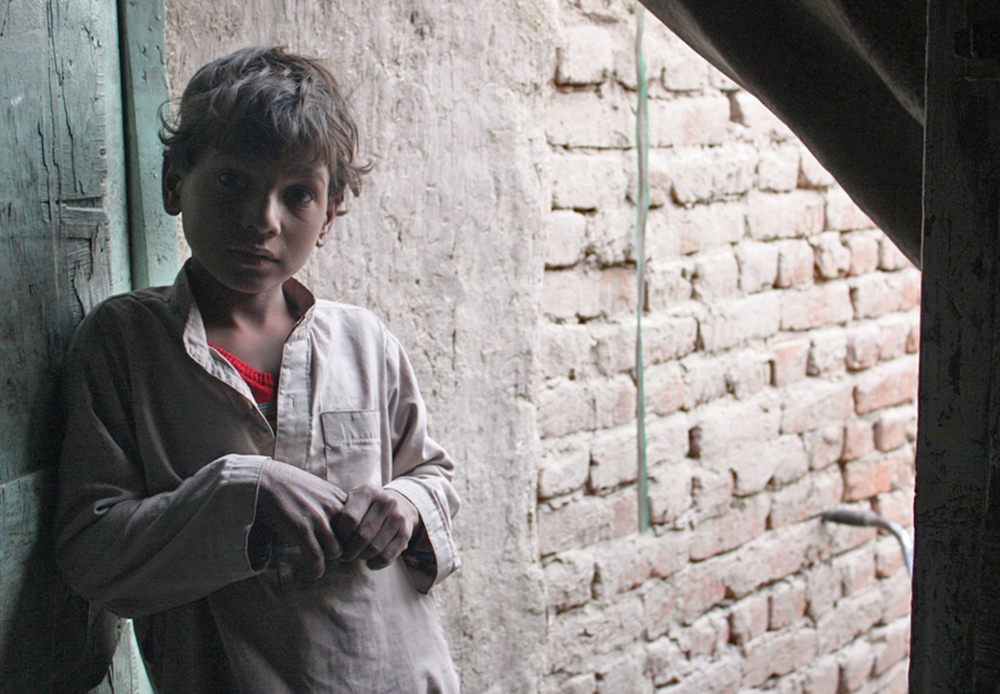 A young Afghan boy stands outside his two-room mud and brick house in an informal settlement of eastern Afghanistan. His family has struggled to re-integrate since returning in 2006 from Pakistan, where they were refugees. This boy was born in Pakistan