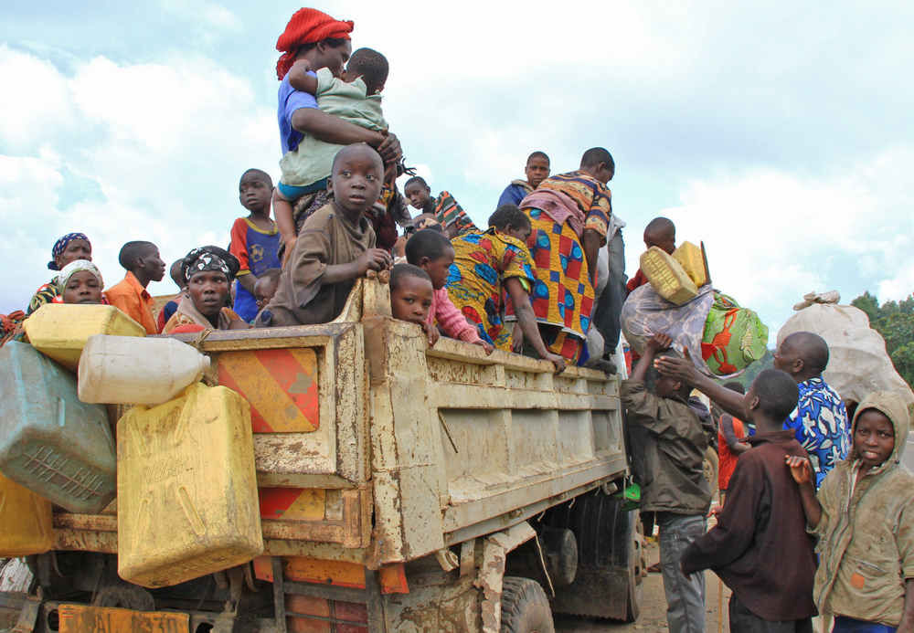 Congolese refugees board a truck at Bunagana on the Uganda-DRC border heading to Nyakabande transit centre in western Uganda's Kisoro District, 19 May 2012. Hundreds of Congolese refugees (30,000-40,000 refugee) have camped at Uganda-Democratic Republic