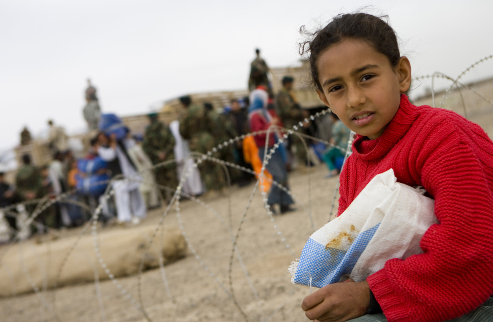 A young girl is watching over the distribution while she guards her own supplies until somebody comes to help her move it. The Humanitarian Aid operation was led by the Afghanistan National Army (ANA) While being over watched by the Americans