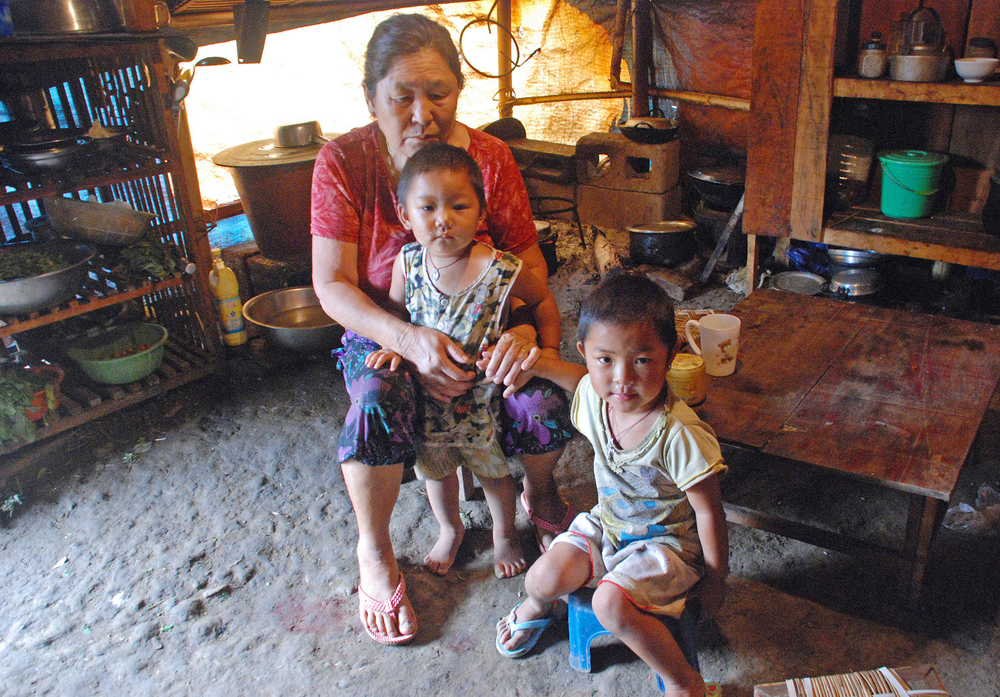 Kachin grandmother Mui Hpu Kaw with two of her seven grandchildren inside the La Ying refugee camp in China's Yunnan province. There are more than 7,000 Kachin displaced in China