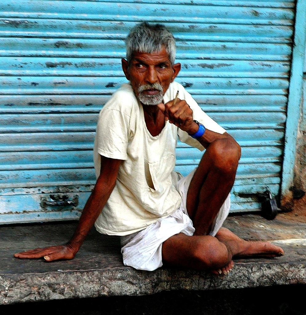 "Indian man smoking an inexpensive, locally-produced cigarette known as ""bidi"", which is a contributing factor in the rise of deaths by non-communicable diseases in places in South Asia"