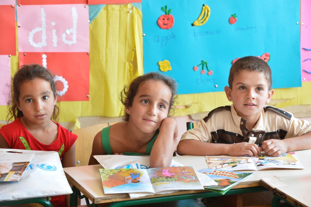 Saadnayel public school - Bekaa/Lebanon. Three Syrian children are looking and listening attentively to their teacher