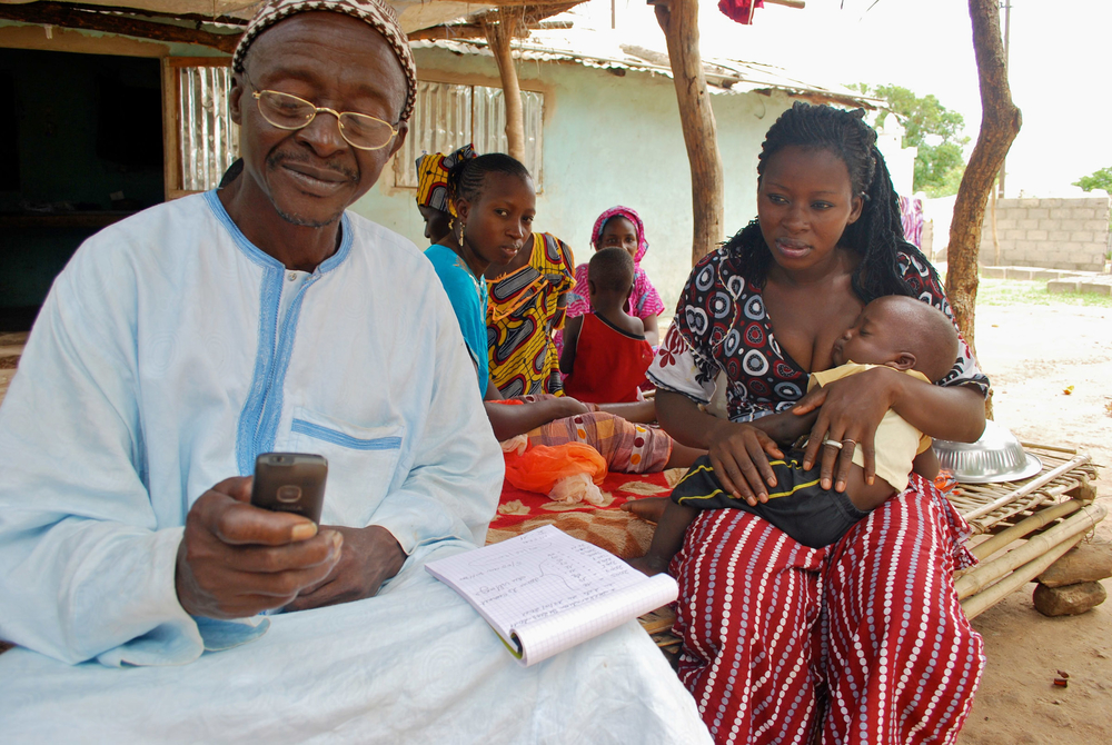 Yaya Kandé (right) deputy village chief in Kolda region, texting details of new born for registration