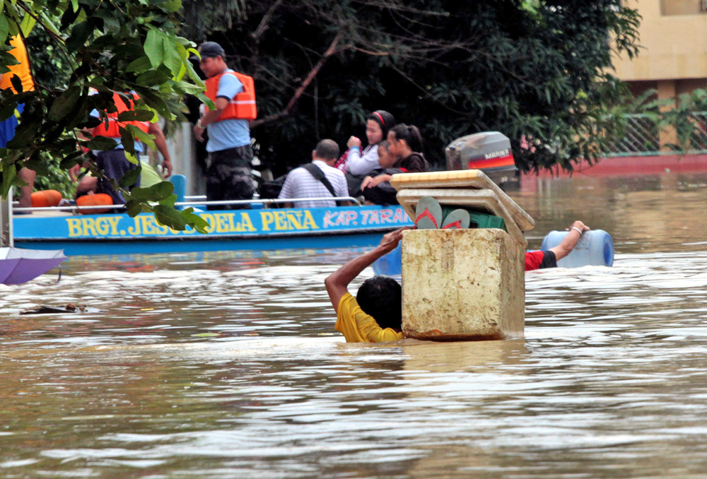 A man carrying his belongings in a styrofoam box tries to reach a rescue boat after flooding in Manila