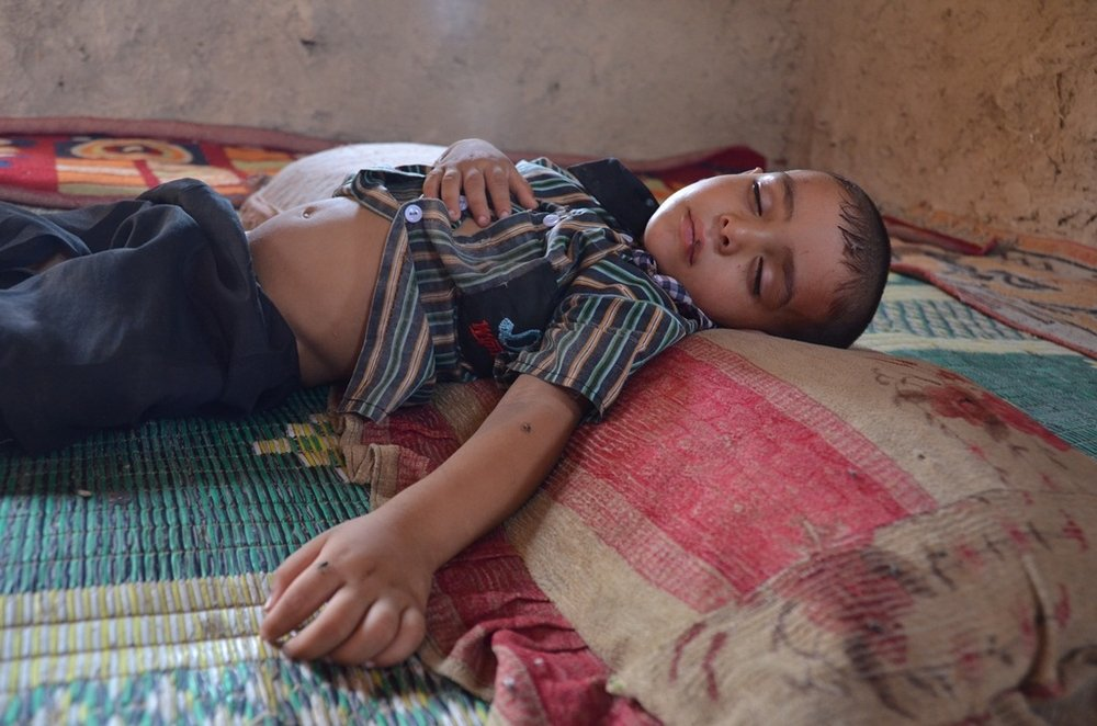 A child sleeps on the floor at al-Rustumiya settlement on the outskirts of the Iraqi capital Baghdad. He is sick but his family cannot afford healthcare. More than 100 families - displaced first by Saddam Hussein's de-Arabization policies, then by Iraq's