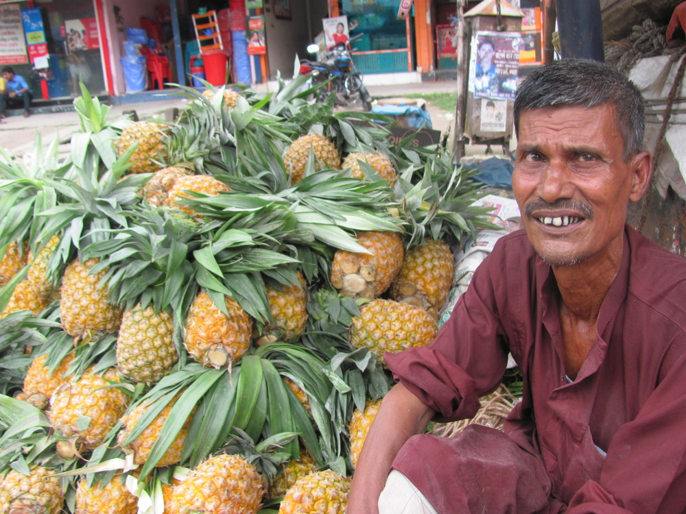 A pineapple farmer sells his wares in a local market in Bangladesh