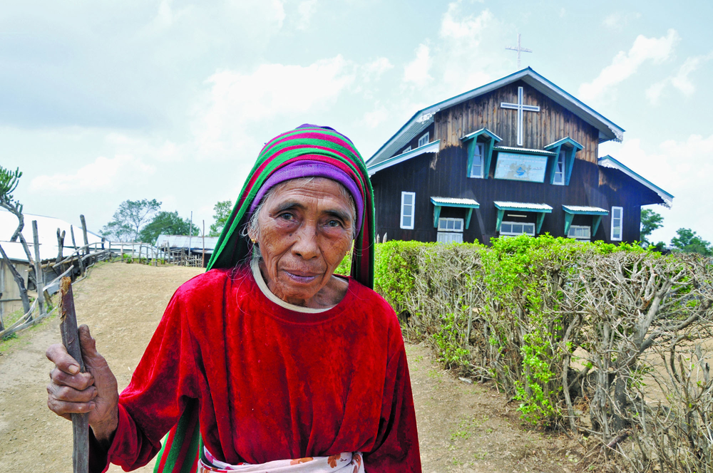An elderly woman and a church in western Chin State. Approximately 90 percent of all Chin are Christian