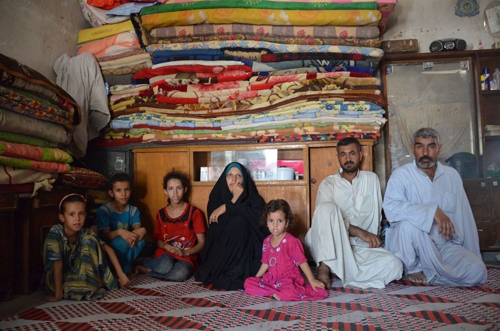 A displaced family sits in their home in Al-Rustumiya IDP settlement on the outskirts of Baghdad. Displaced by Saddam Hussein's de-Arabization policies and then again by the sectarian conflict of 2006-7, the family lives here without proper water, electri