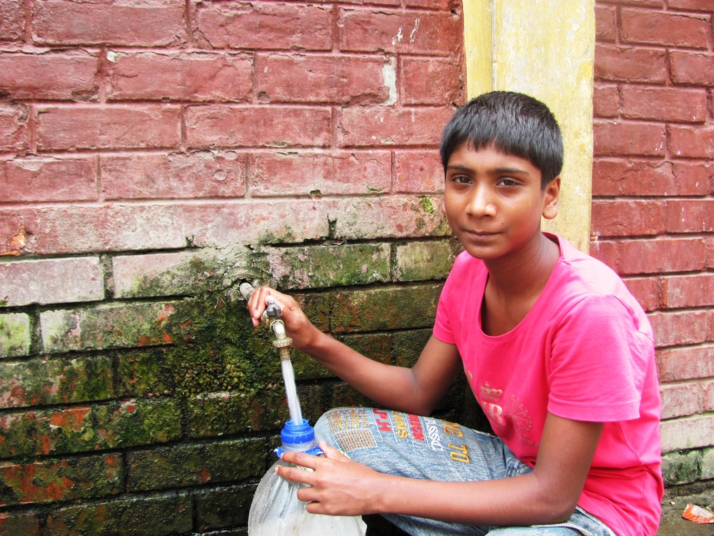 A young boy fills a plastic water container in Dhaka. Millions face difficulty accessing water in the capital